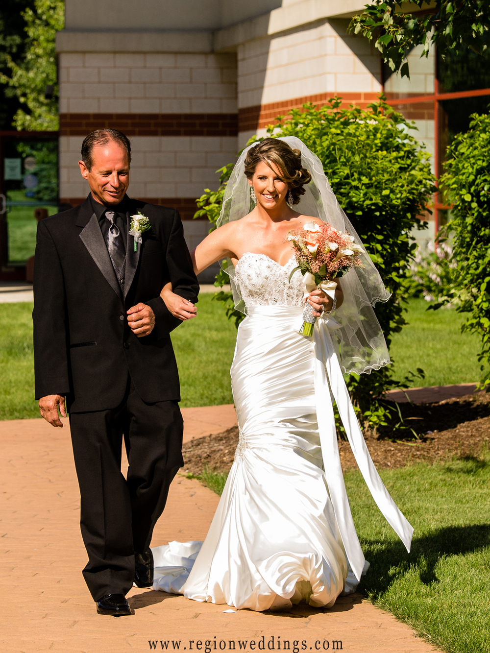 The bride makes her entrance at an outdoor ceremony at the Halls of St. George.
