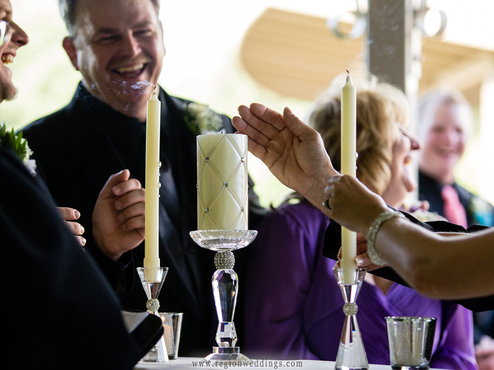 Family attempts to keep the unity candles lit at an outdoor wedding ceremony.