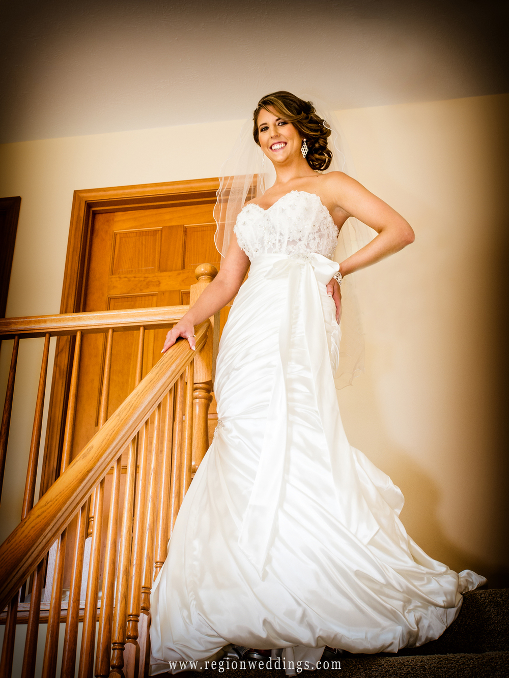 The bride shows off her dress on the steps of her home in Cedar Lake on her wedding day.