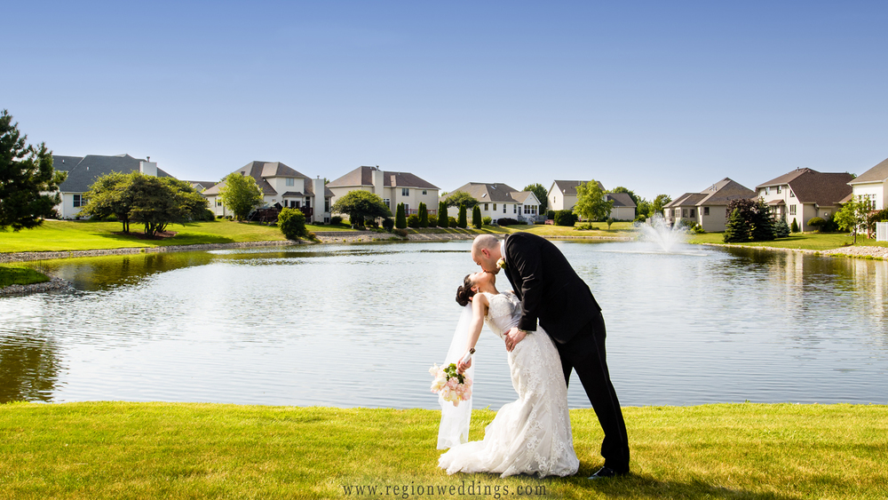The groom dips his bride in front of the beautiful lake inside the Ellendale Farm neighborhood in Crown Point, Indiana.