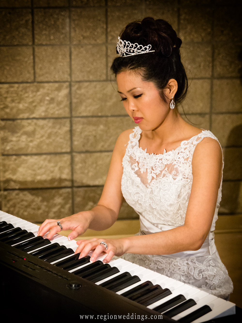 The bride plays piano during dinner hour at her wedding reception at Trinity Lutheran Family Center in Merrillville.