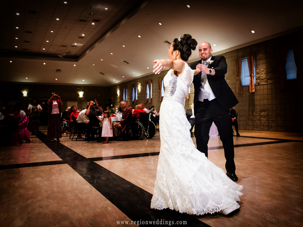 A Korean bride and American groom dance at their wedding reception at Trinity Lutheran Family Center in Northwest Indiana.
