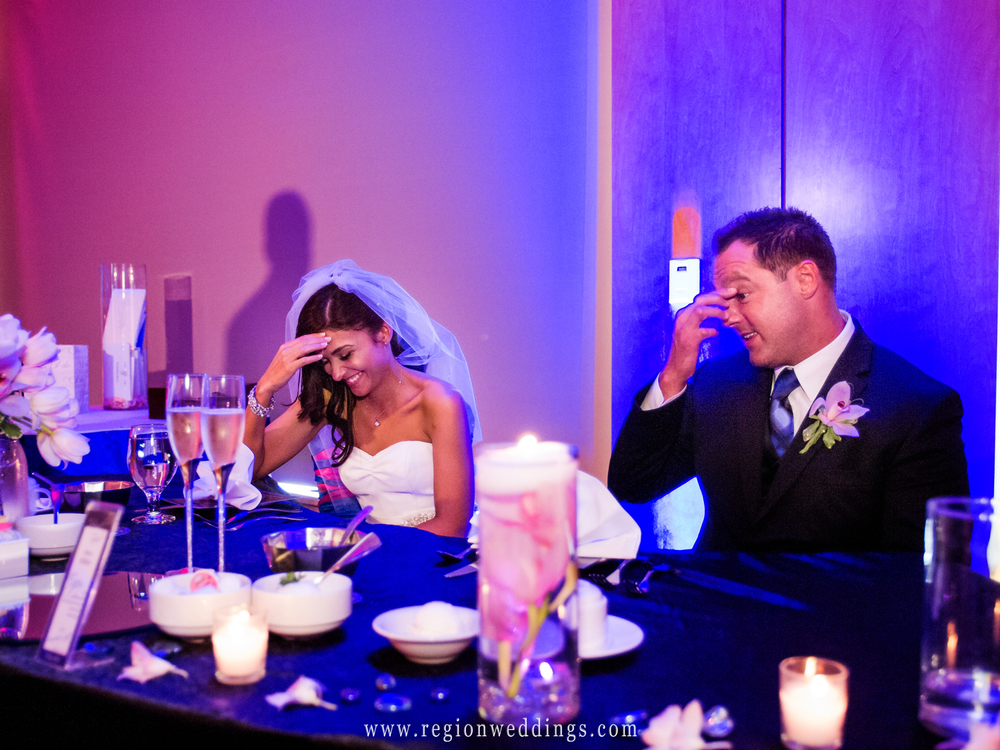 The bride and groom act embarrased at a funny moment during a toast at their wedding reception at Centennial Park.