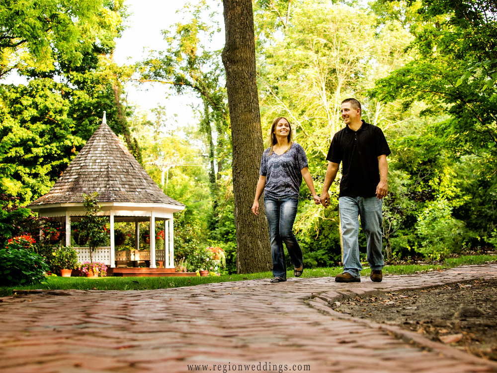 A couple in love stroll in front of the gazebo at Deep River Park in Hobart, Indiana during an engagement photo session.