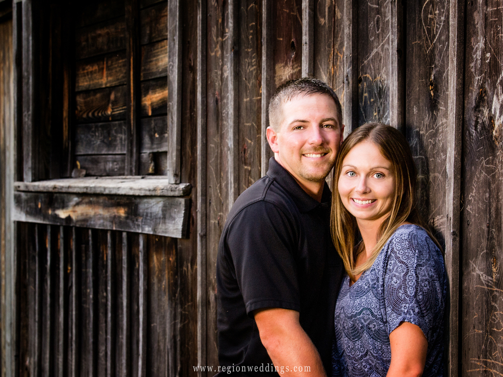 An engaged couple poses alongside an old barn in Valparaiso, Indiana.