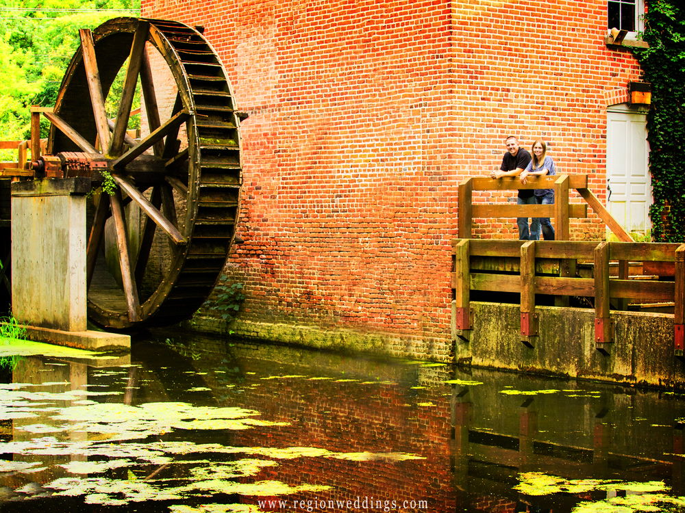 A couple poses alongside the water wheel at Deep River Park for their engagement photo.