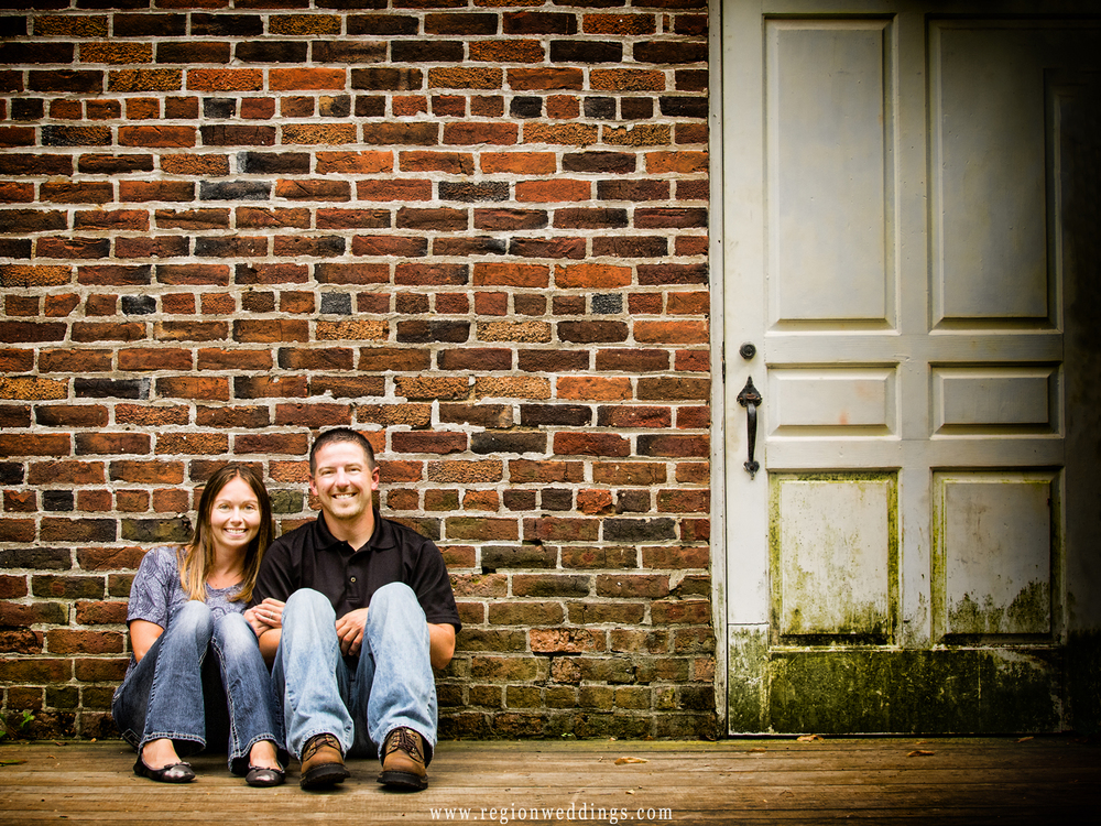 An engaged couple poses against a grungy brick wall at Deep River County Park.