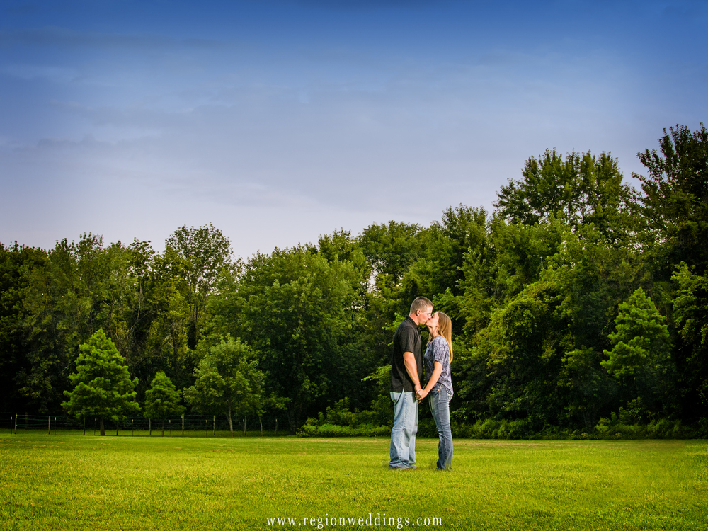 A couple embraces in a large green field in the depths of Deep River Park.