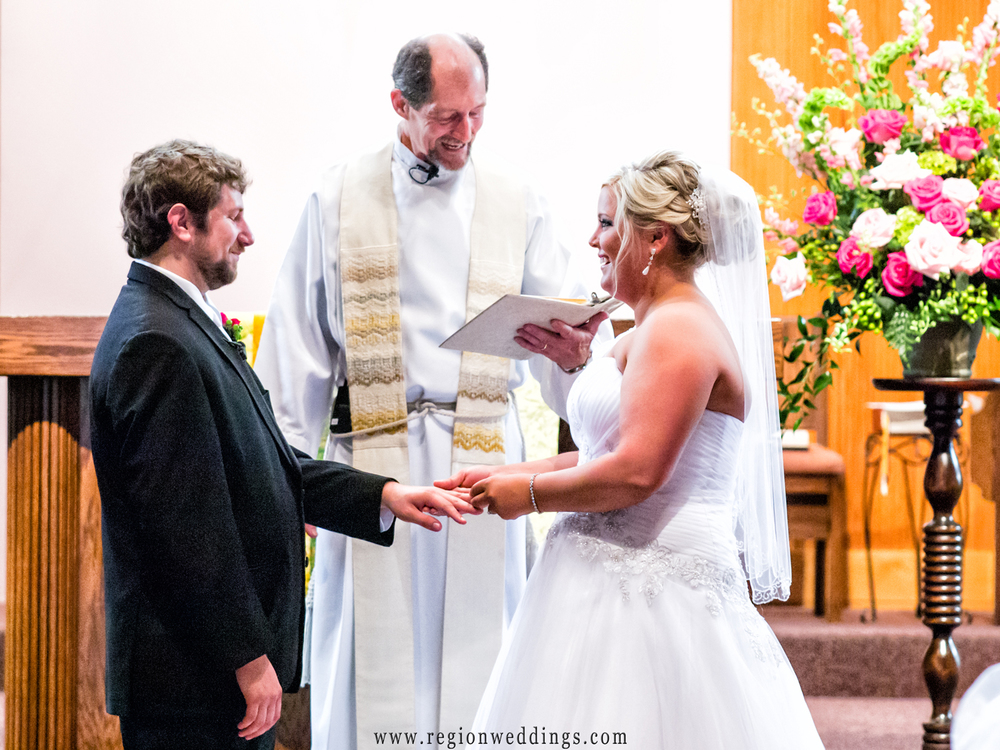 The bride places a wedding band upon the groom's finger during their church wedding ceremony.