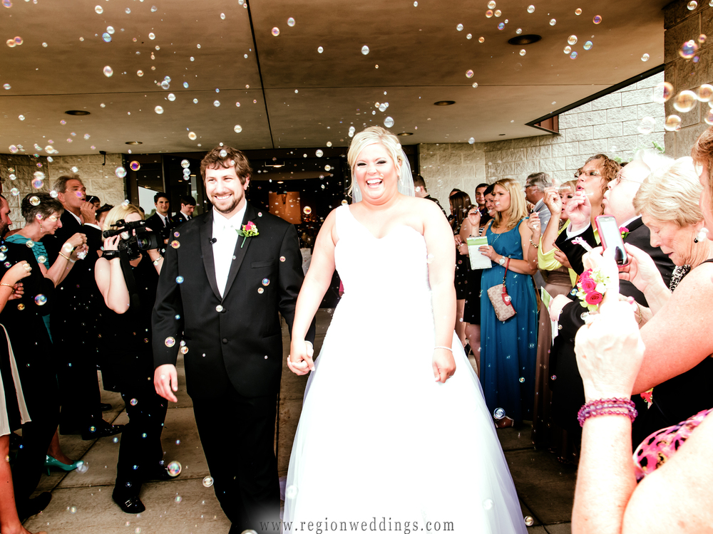 The bride and groom exit the church as family and friends shower them with bubbles.