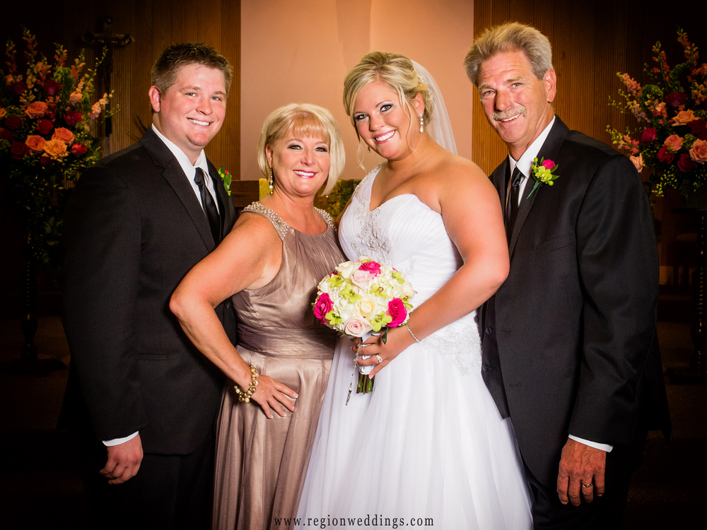 Formal wedding photo for the bride and her parents.