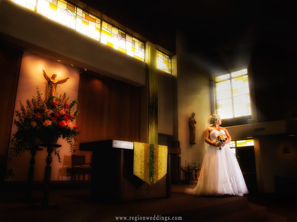 A dramatic looking wedding photo of the bride alone at the altar of a Valparaiso church.