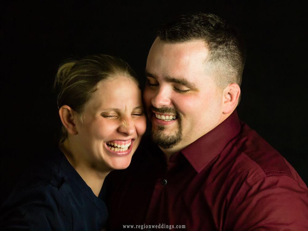 A couple laughs it up for a fun engagement photo in a Crown Point portrait studio.