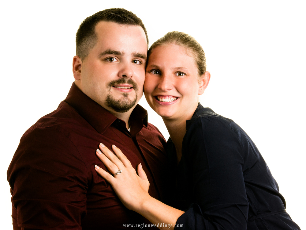 A bride to be shows off her ring in a studio engagement photo taken in Crown Point, Indiana.
