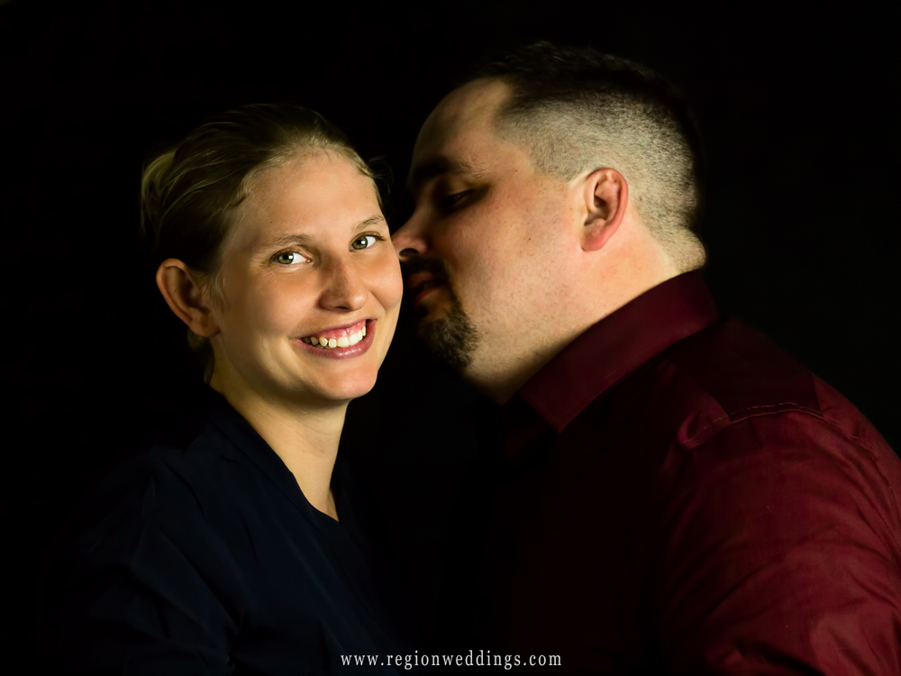 The groom to be whispers into his bride to be's ear during a studio engagement session.