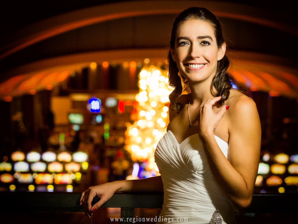 The bride smiles as the casino lights of Blue Chip in Michigan City shine behind her.