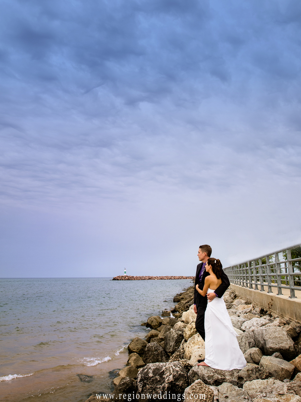 A dark and dramatic sky looms over the bride and groom for their wedding photo at Portage River Walk.