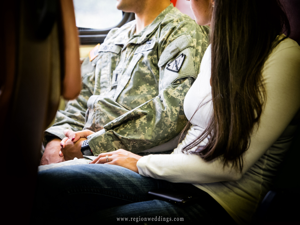 An engaged couple holds hands on the train as they make their way to Chicago.