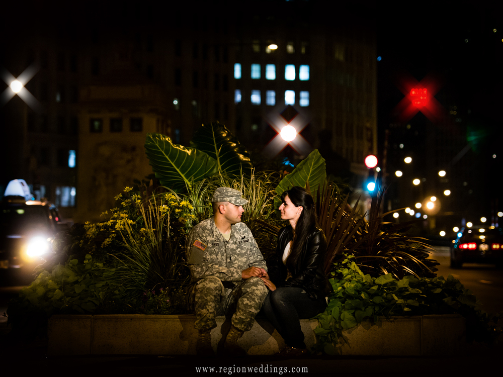 A couple sit in the center median of Michigan Avenue at  night with car lights surrounding them.