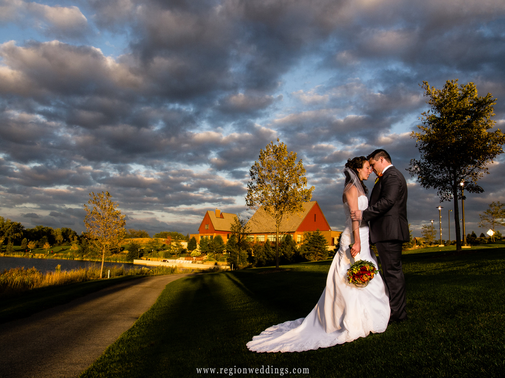 The bride and groom are illuminated by Fall colors and a dramatic sky at Centennial Park in Munster, Indiana.