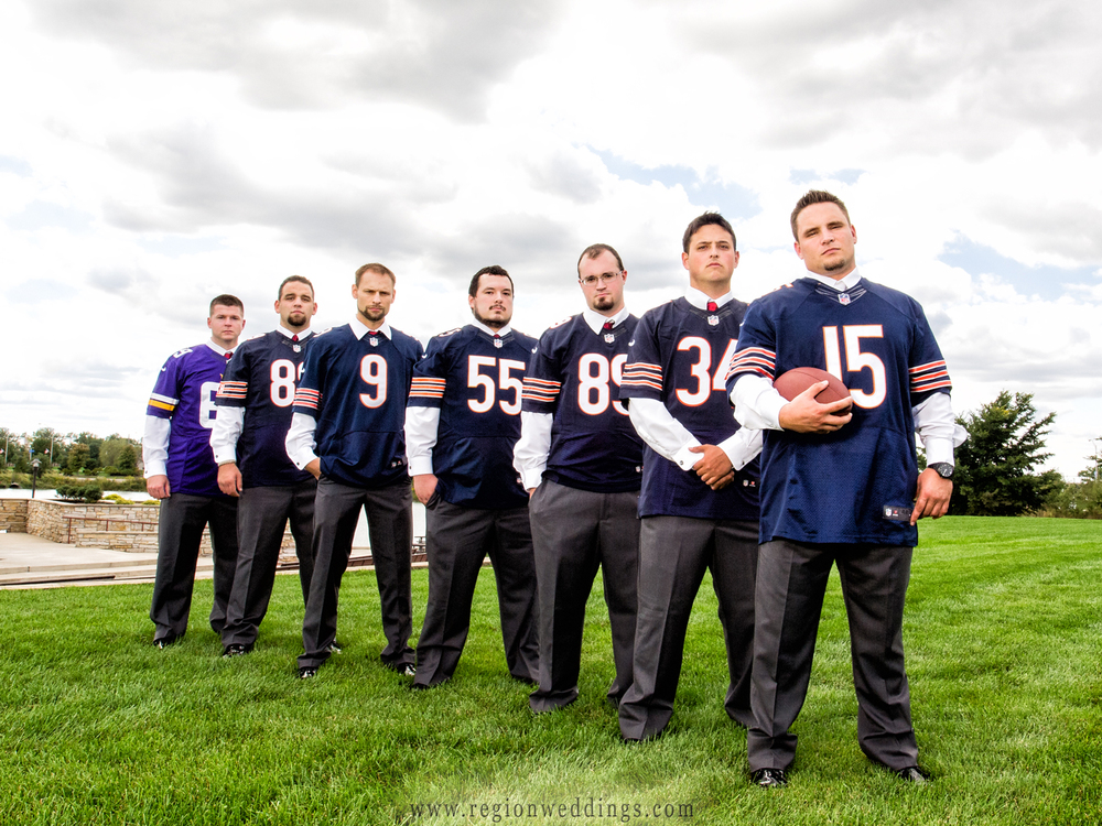 Groomsmen pose in football jerseys for a wedding photograph.