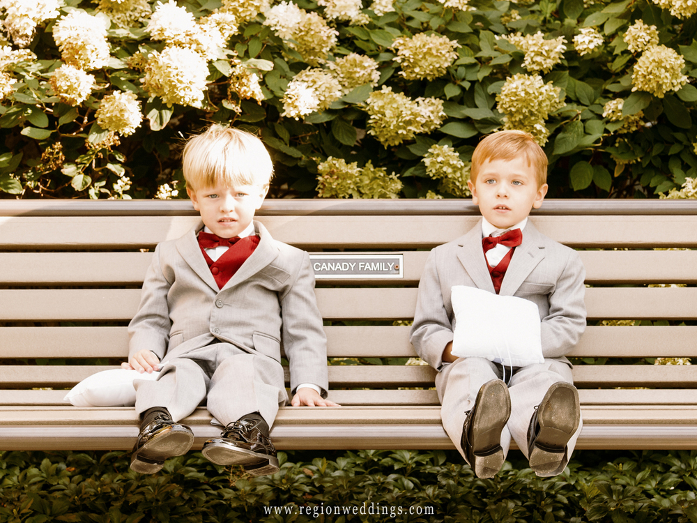 Ring bearers take a break on a bench at an outdoor Fall wedding ceremony.