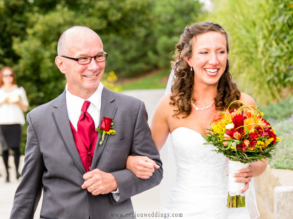 A bride is overcome with joy as she walks down the aisle with her father at an outdoor autumn wedding ceremony.