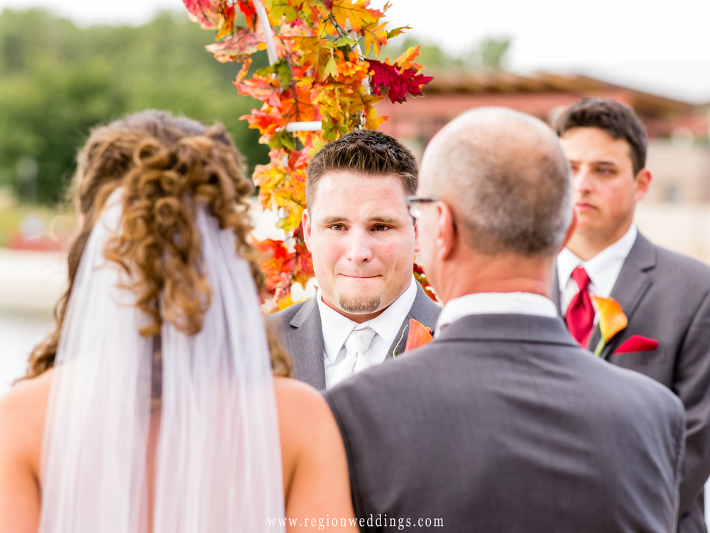 An emotional groom begins to tear up as the bride's Father give her away.