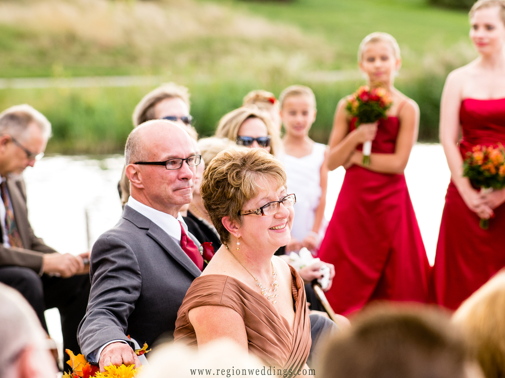 Family of the bride watch as their daughter gets married in a Fall wedding ceremony.