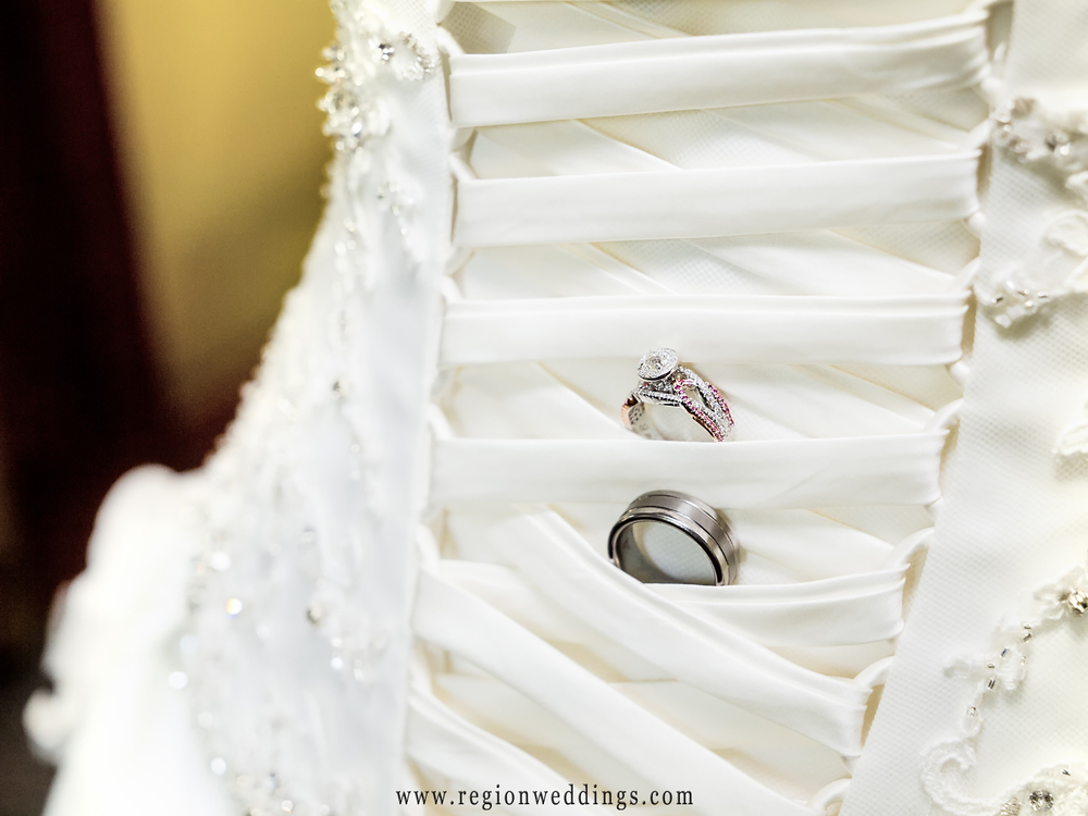 Wedding rings tucked into the lacing of the bride's dress.