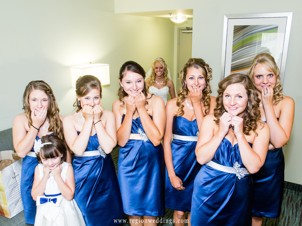 The bridesmaids are filled with excitement as they anticipate their first look of the bride in her wedding dress.