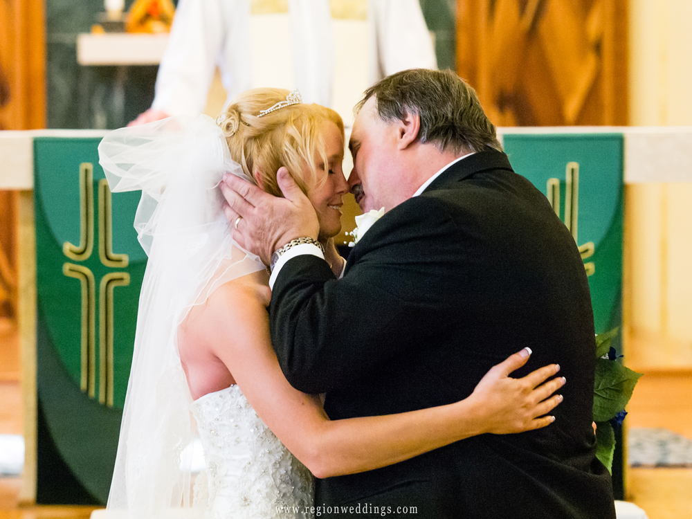 The bride's father gives her away at the altar during a church wedding ceremony.