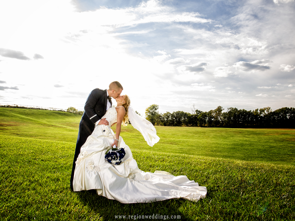 A soldier dips his bride and the wind makes her veil float behind her in this wedding photo taken at Oak Ridge Prairie County Park in Griffith.