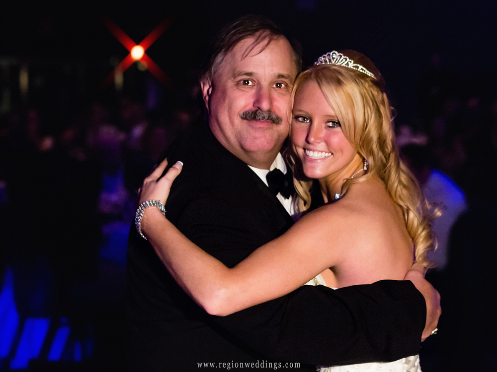 The bride and her father smile on the dance floor at her wedding.