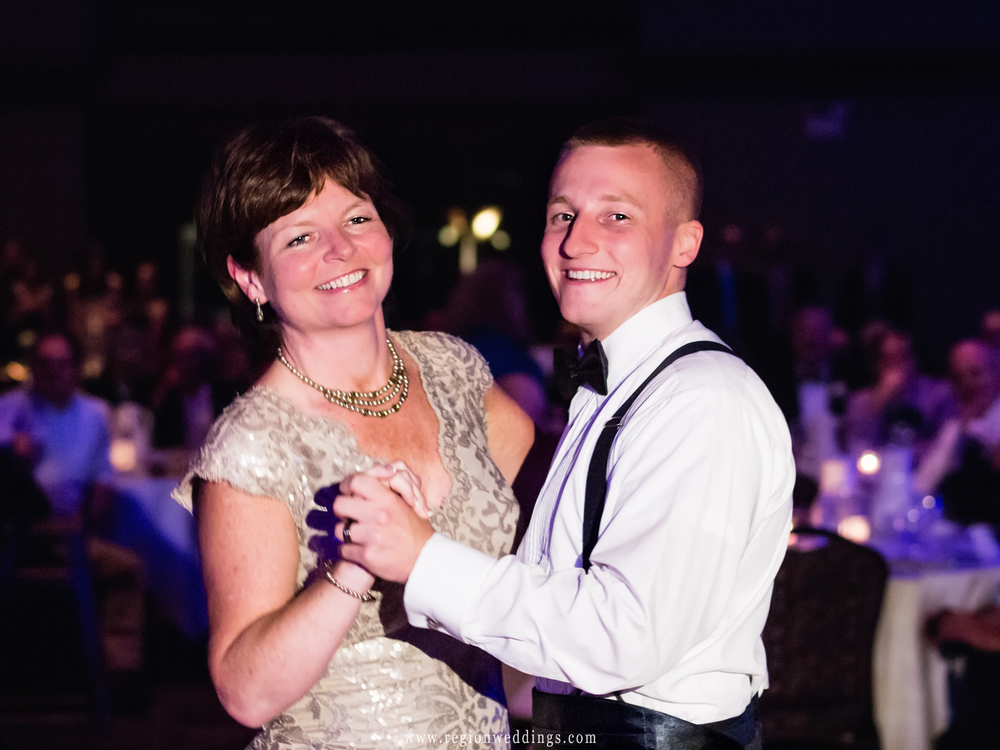 The groom and his mother smile on the dance floor at the Halls of St. George.