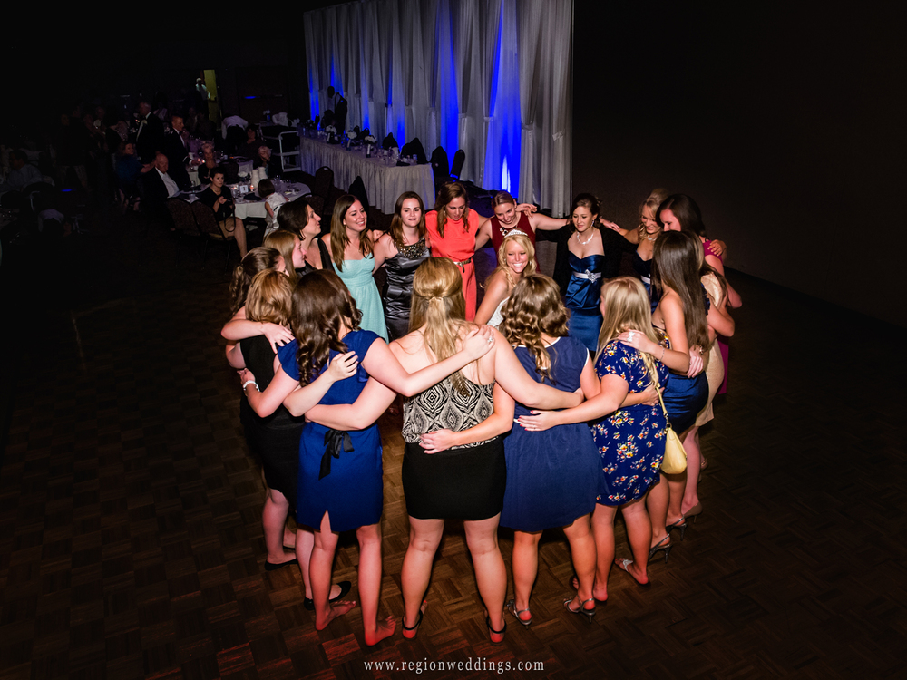 Sorority sisters surround the bride on the dance floor at her wedding.
