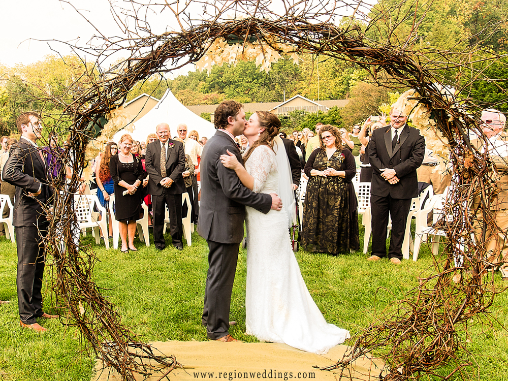 The bride and groom are surrounded by family for their first kiss captured from behind and showing their guests in the background.