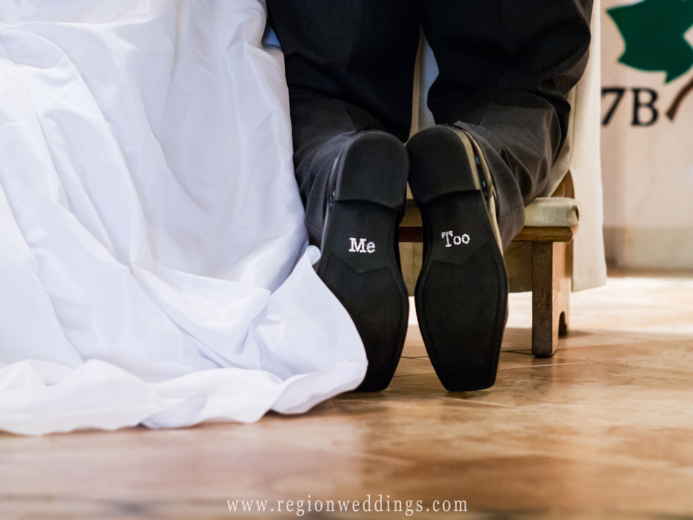 The groom shoes engraved with the words 'me too' are shown as he kneels down at the altar during a church wedding ceremony.