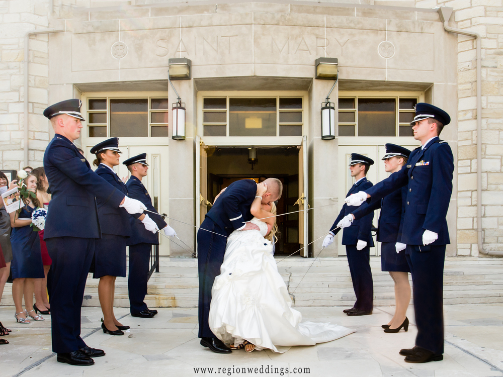 A newly married couple dips as the Air Force Honor Guard salutes them with sabers.