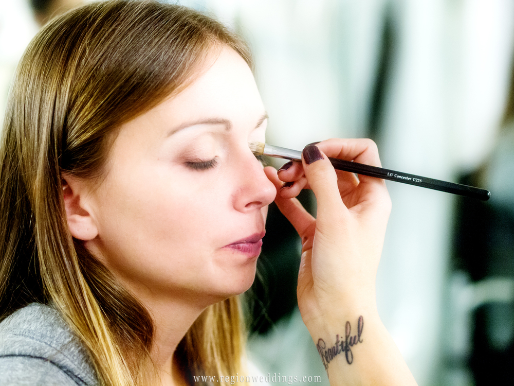 """The make up artist applies eyeliner to the bride revealing a tattoo of the word """"beautiful""""."""