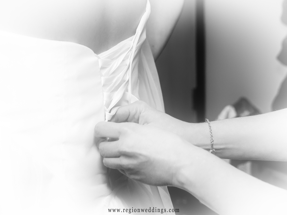 The bride's maid of honor helps tie the lacings on the wedding dress.