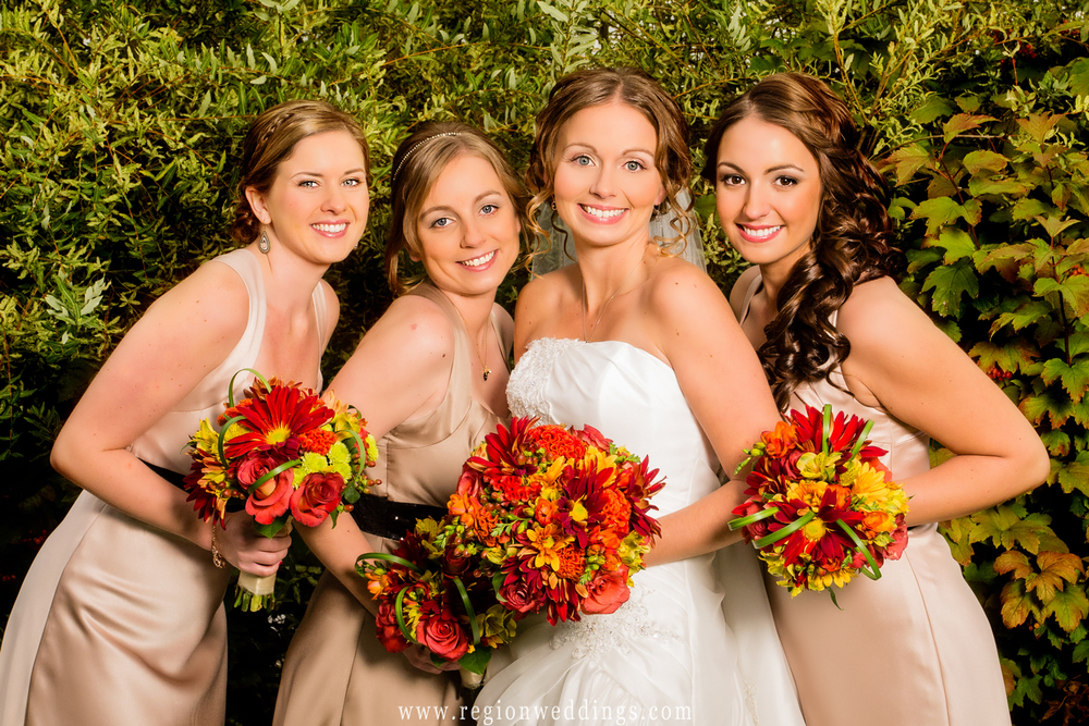 Bridesmaids give a group hug to the bride while surrounded by Fall colors.