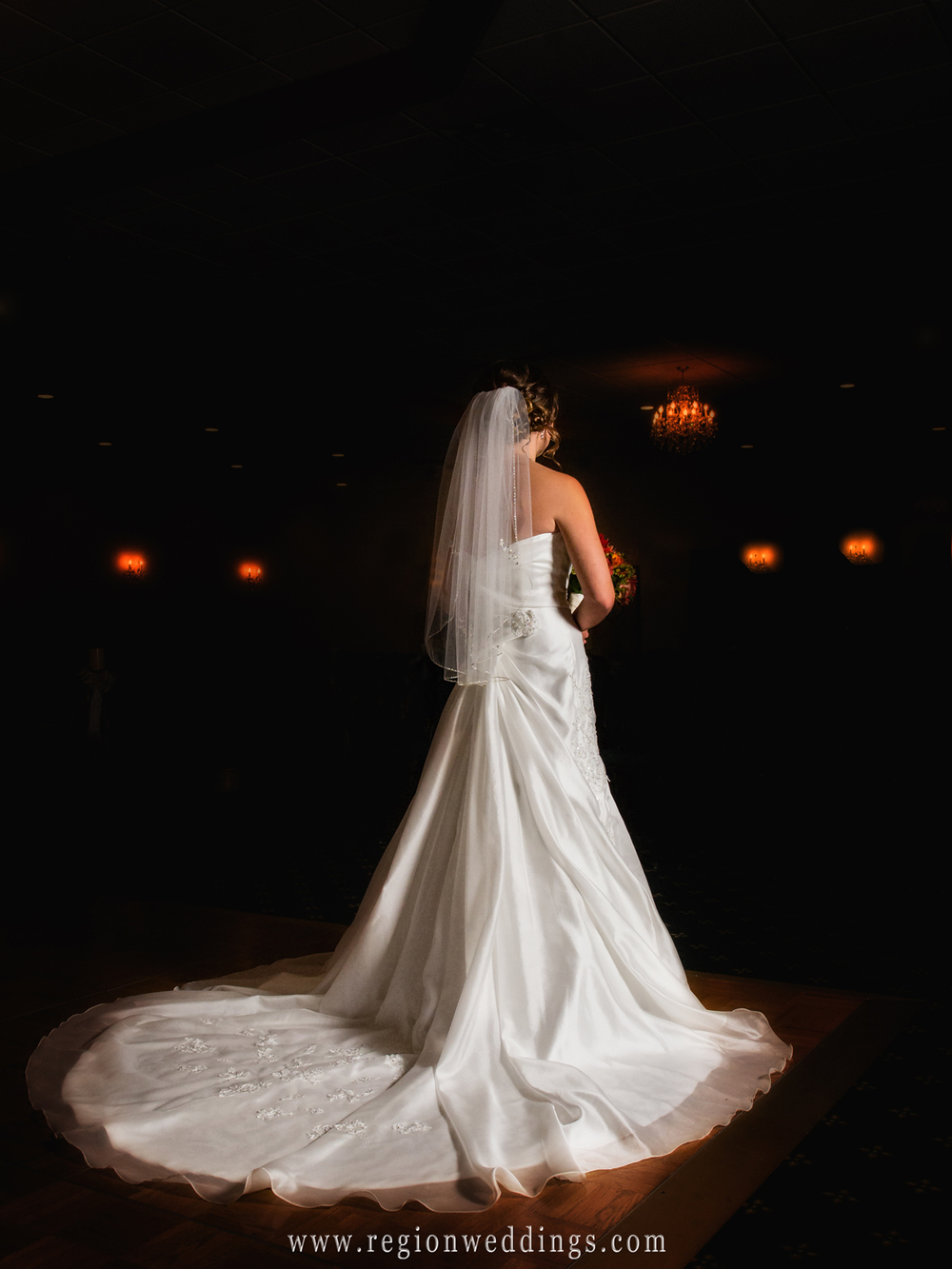 The bride shows off the back of her dress in a darkened room with orange hued candles.