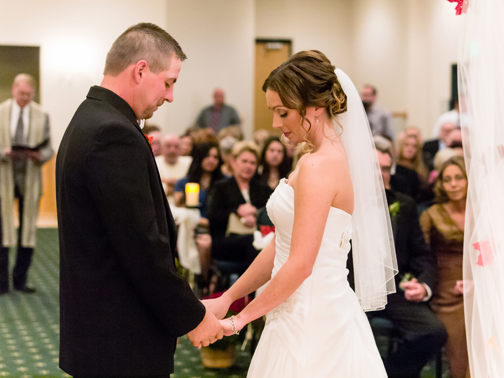 the bride and groom solemnly pray during their indoor wedding ceremony at The Patrician banquet hall.