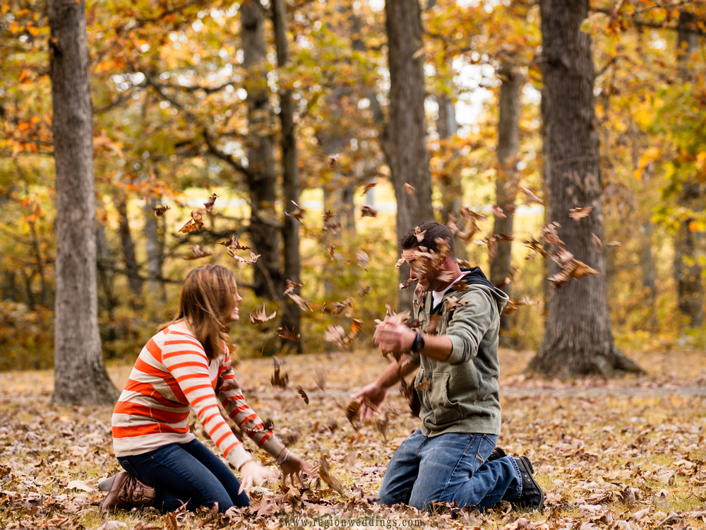 An engaged couple has fun throwing leaves at each other during their engagement photo session at Lemon Lake County Park.