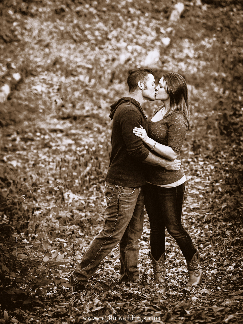 A couple in loves kisses romantically while walking in the woods.