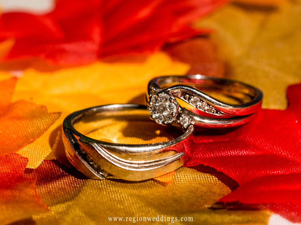 Wedding rings sit atop orange and yellow Autumn leaves.