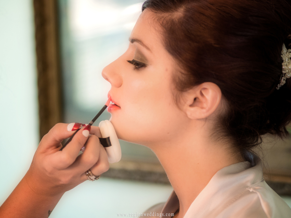 A bride has lip gloss applied while getting ready for her wedding.
