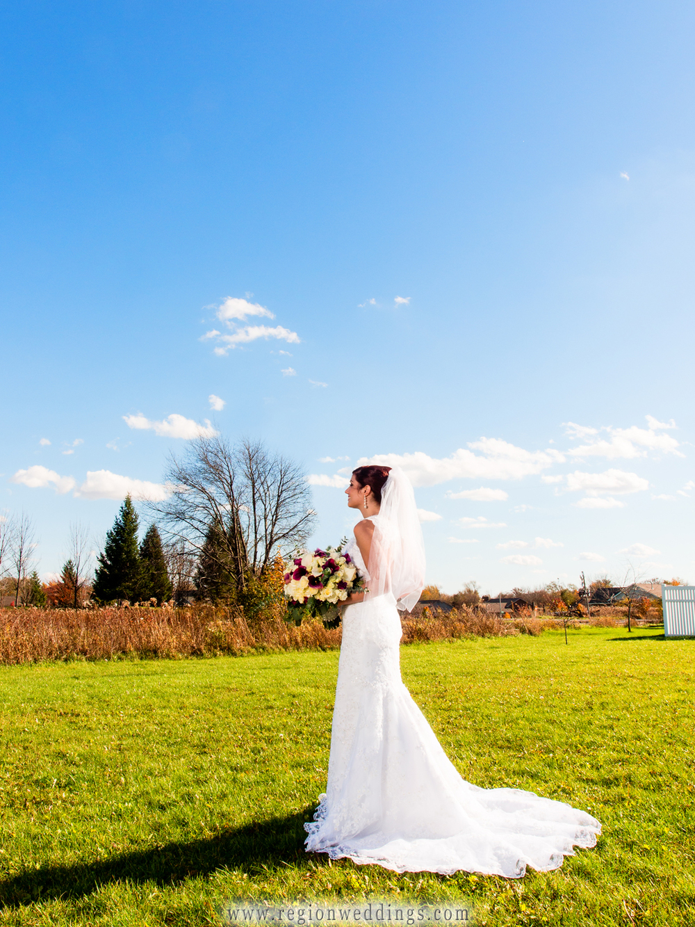 A beautiful bride shows off her dress underneath the blue skies on the morning of her wedding.