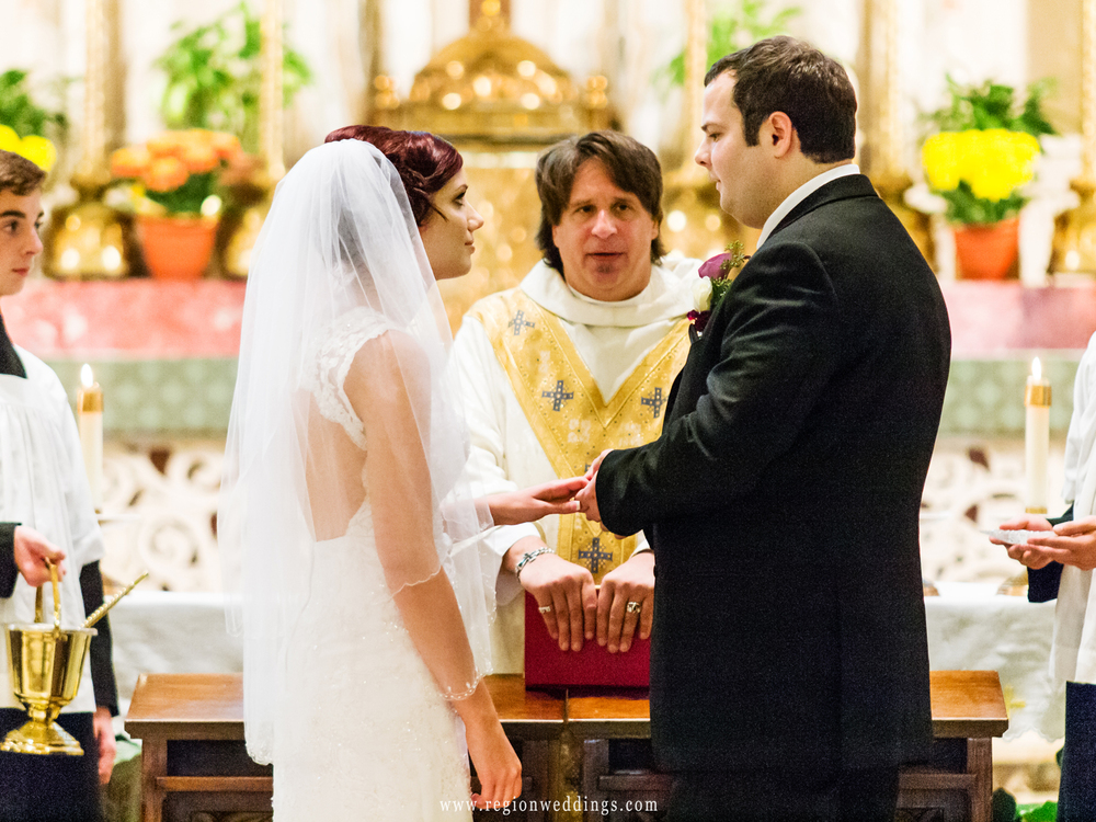 The bride and groom exchange rings on the altar of St. Andrew.